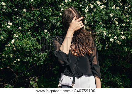 Beautiful Stylish Hipster Girl With Beautiful Windy Hair Having Fun At Floral Bushes In Sunny Day. B