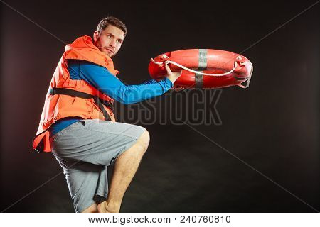 Lifeguard In Life Vest Jacket Throwing Ring Buoy Lifebuoy. Man Supervising Swimming Pool Water On Bl