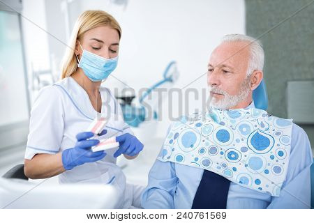 Female Dentist Shows Patient Appearance Of Tooth