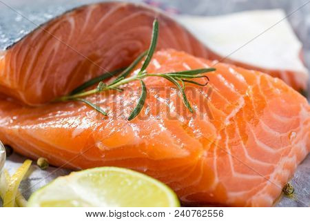 Raw Salmon Steaks With Aromatic Herbs And Spices On White Paper. Healthy Food Concept.