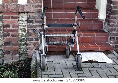 Mobility Walker Parked At The Bottom Of An Exterior Flight Of Red Tiled Steps On A Garden Walkway
