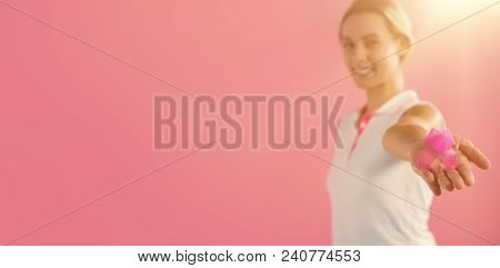 Portrait of woman holding pink ribbon