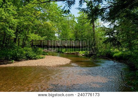 A pedestrian footbridge over a slow moving river in rural Nova Scotia, Canada.
