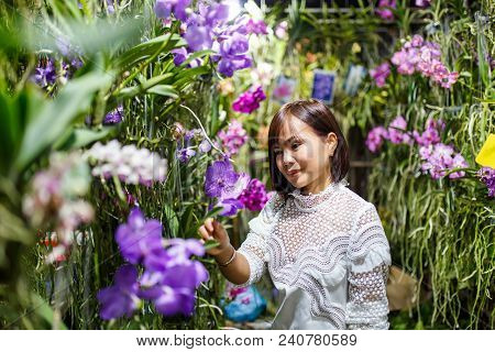 Smiling Young Asian Woman Contemplating Orchids In Floral Shop