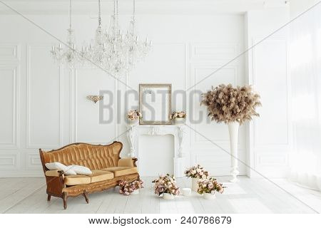 Beautiful Classical White Interior With A Fireplace, Brown Sofa And A Vintage Chandelier. Retro, Cla