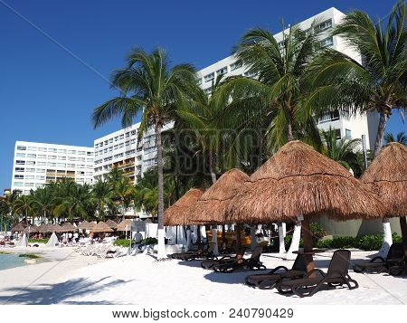 Cancun, Mexico North America On March 2018: Sunbath Places Under Umbrellas, Palm Trees On Tropical S
