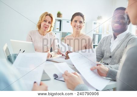 Cheerful multi-ethnic team of managers analyzing results of accomplished work with help of statistic data while gathered together at boardroom illuminated with sunbeams