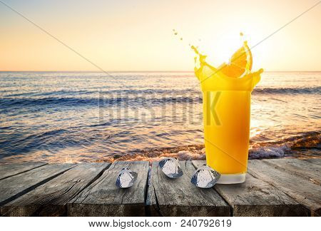 Glass Of Orange Juice With Splash From Orange Slice And Ice Against The Background Of The Sea. Glass