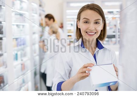 Responsible Employee. Merry Female Pharmacist Smiling To Camera And Holding Drug