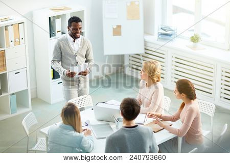 Handsome African American manager with toothy smile presenting his creative ideas to colleagues while having working meeting at spacious boardroom