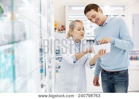 Special Prescription Drug. Professional Female Pharmacist Using Tablet While Communicating With Man