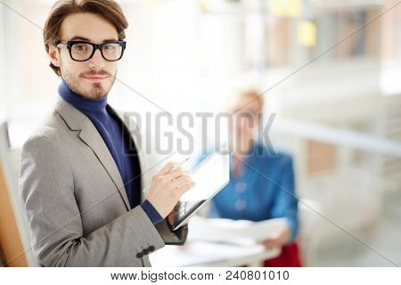 Portrait shot of smiling bearded designer holding digital tablet in hands and looking at camera while having working meeting in boardroom