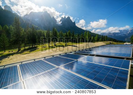 Solar Cell Panel In Country Landscape Against Sunny Sky And Mountain Backgrounds. Solar Power Is The