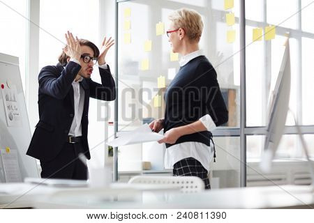 Emotional young manager standing at marker board and gesticulating vigorously while trying to explain something to his middle-aged superior, interior of open plan office on background