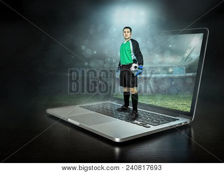 Caucassian soccer Player with ball in a professional sport game play on the laptop in football under stadium lights.