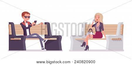 Young Man And Woman Sitting On Bench. Handsome Caucasian Millennial Boy And Attractive Blonde Girl W