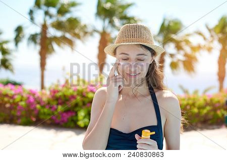 Portrait Of A Beautiful Young Woman, Smiling In A Swimsuit Smeared Face With Sun Protection Cream In