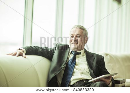 Lawyer With Digital Tablet Sitting On The Sofa In The Private Office. The Photo Has A Empty Space Fo