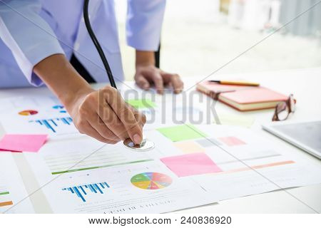 Doctor Holding Stethoscope To Graph Discussion And Analysis Data Charts And Graphs.financial Analysi