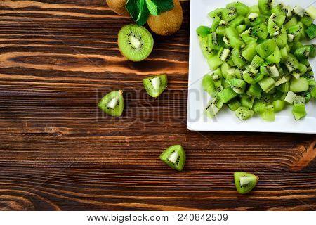 Freshly Sliced Kiwi Fruit With Whole Kiwis In Background.