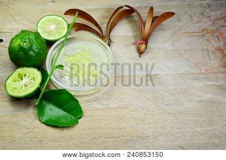 Sliced Bergamot And Green Leaf With Bergamot Meat In Translucent Dish On Wooden Table