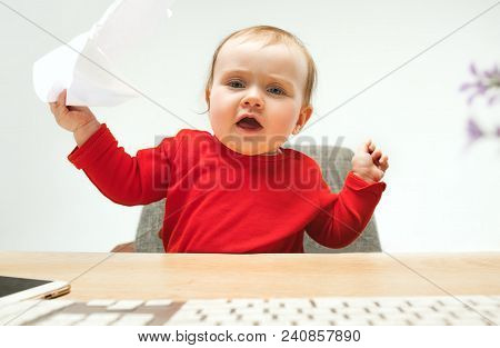 I Am Boss. Child Baby Girl Sitting With Keyboard Of Modern Computer Or Laptop In White Studio Backgr