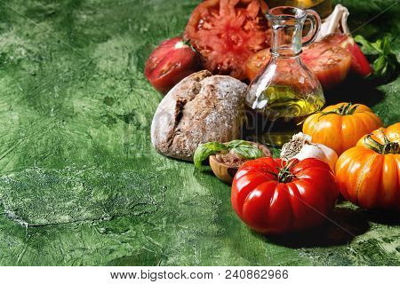 Variety Of Red And Yellow Organic Tomatoes With Olive Oil, Garlic, Salt And Bread For Salad Or Brusc
