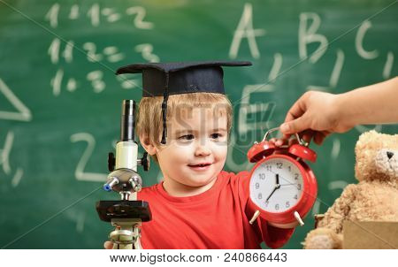 Kid Boy In Academic Cap Near Clock In Male Hand, Classroom, Chalkboard On Background. School Break C