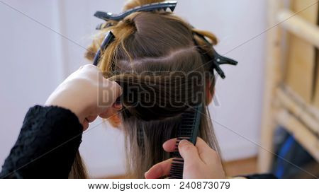 Professional Hairdresser, Stylist Combing Hair Of Female Client With Long Hair In White Make Up Room