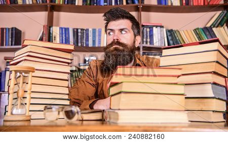 Man On Strict Face Sit Between Piles Of Books, While Studying In Library, Bookshelves On Background.