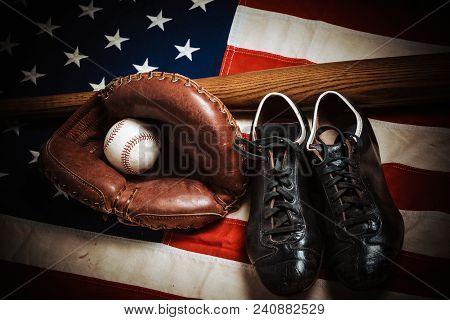 A Group Of Vintage Baseball Equipment, Bats, Gloves, Baseballs American Flag Background