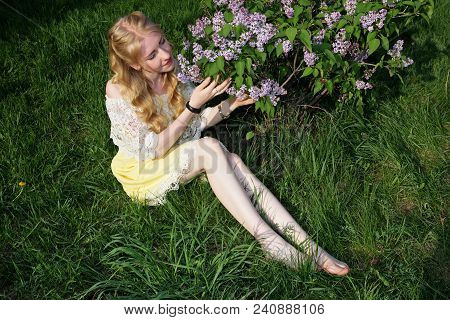 Young Barefoot Girl Sitting On The Green Grass And Admiring The Flowers Of Lilac.
