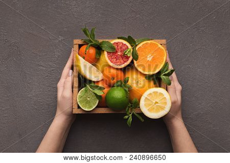 Hands Holding Citrus Fruits In Box On Gray Background. Assortment Of Exotic Citruses, Top View, Copy