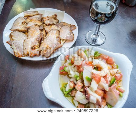 Plates Of Tapas And Glass Of Red Wine In Sevilla In Spain