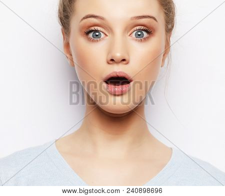 Indoor shot of stupefied shocked blonde woman keeps mouth widely opened, looks   at camera, wears casual clothes, isolated over white  background. Attractive female model indoor.Lifestyle concept.