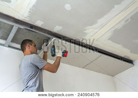 Construction Worker Assemble A Suspended Ceiling With Drywall And Fixing The Drywall To The Ceiling