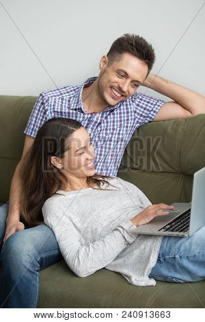 Happy Couple Smiling Watching Family Video At Laptop Together, Woman Lying On Husbands Knees Using C