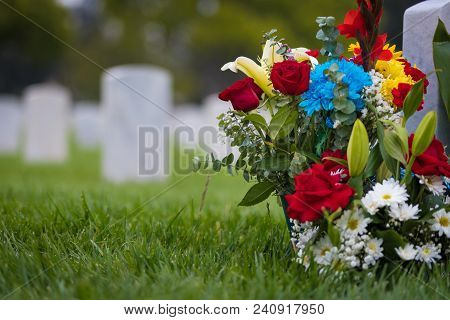 White Grave Markers And Flowers At A National Cemetary