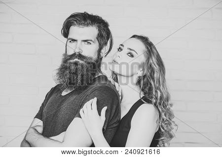 Man With Beard And Woman With Long Blond Hair. Girl And Bearded Hipster. Couple In Love Hug On White