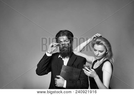 Serious Couple Of Young Blond Woman In Black Dress With Smartphone And Handsome Bearded Hipster Man