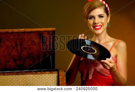 Retro woman with music vinyl record and gramophone. Pin-up retro female style portrait. Girl pin-up style wearing red dress. Retro style is one of most relevant. Classical music versus modern.