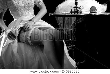 Wedding night preparing garter. Bride undressing and put veil on table. Candle illuminates house. Girl choosing stocking before wedding. Memories of mother about wedding. Black and white old photo.