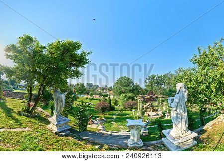 Courtyard In A Village In Transylvania Romania With Statue Replicas Copy Space Available Over Sky