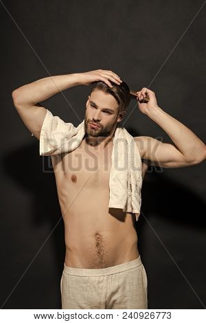 Macho With Bath Towel In Sexy Underwear. Man Brush Hair With Hairbrush On Black Background. Haircare