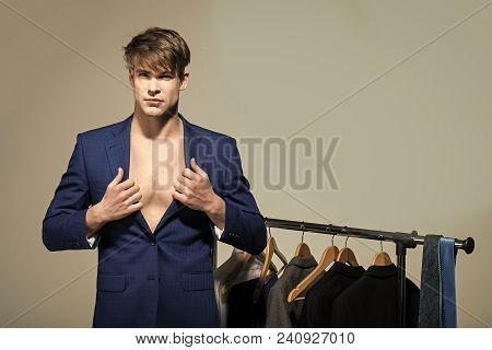 Man Wear Formal Blue Suit On Bare Chest In Wardrobe On Grey Background. Business Fashion, Style Conc