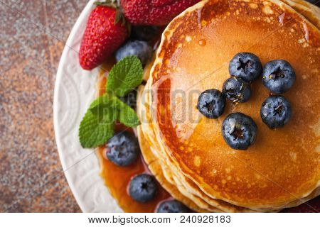 Close-up Delicious Pancakes, With Fresh Blueberries, Strawberries And Maple Syrup On A Rusty Backgro
