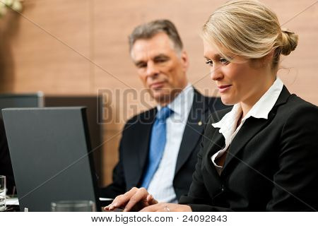 Lawyer with his secretary in his office, he obviously is dictating something