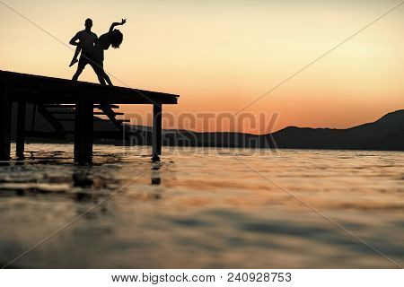 Silhouette Of Sensual Couple Dancing On Pier With Sunset Above Sea Surface On Background. Romance An