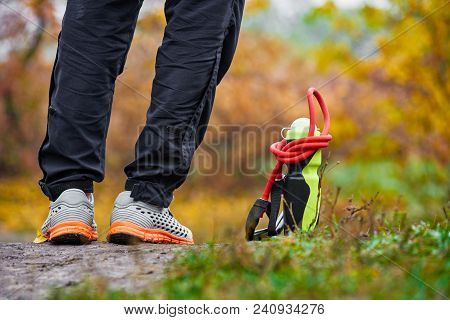 Closeup Of Sportsman Legs In Sneakers With Bottle And Expander