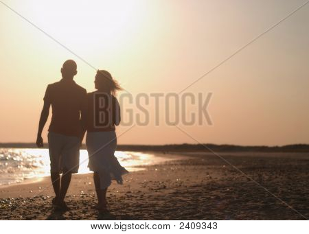 Couple Walking On Beach.